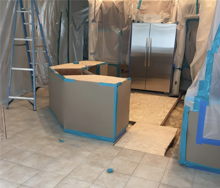 a kitchen with tarping around the cabinets