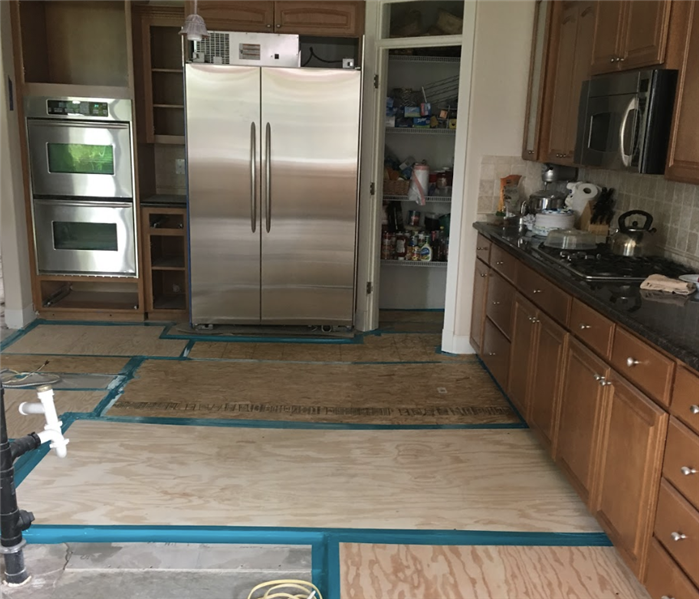 a kitchen during demolition with flooring removed