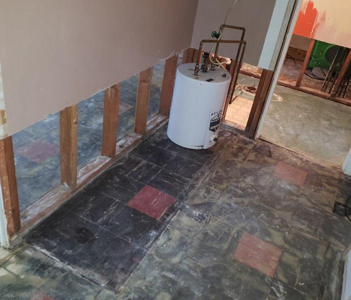 a hallway with removed flooring and baseboards and sheetrock removed from lower part of the wall